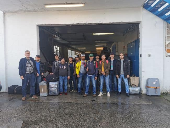 The crew of the MV Diavlos Force stop for a group photo as they leave the vessel on their way home